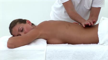 massages : Pretty woman enjoying a back massage in a spa center Stock Footage