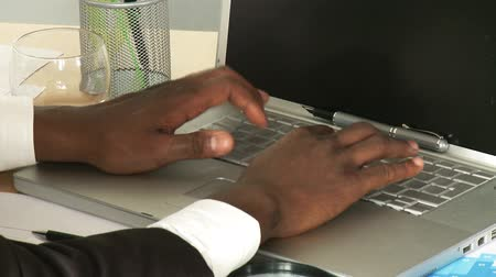 business man : Close-up of an Afro-American businessman typing on a laptop footage Stock Footage