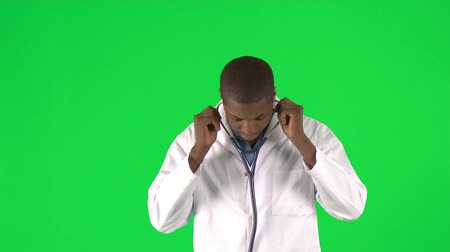 operacja plastyczna : Footage of an Afro-American male doctor using his stethoscope against green screen in high definition