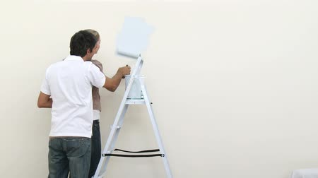 swatches : Footage in high definition of attractive couple painting a room in new house Stock Footage