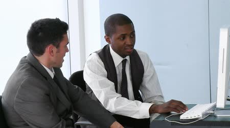 afro amerikai : Footage of an Afro-American businessman explaining to his colleague the work with a computer in office in high definition