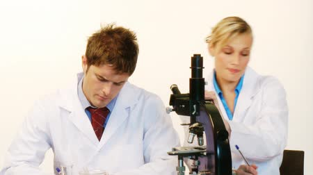 keşif : Attractive male and female scientist working together looking through a microscope in a laboratory in High Definition Stok Video