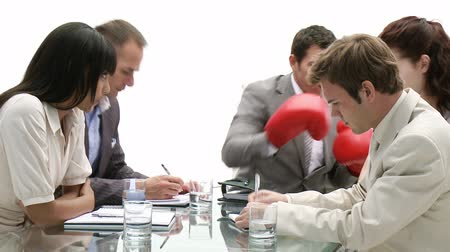 puncs : Stressed manager wearing boxing gloves in a meeting  Stock mozgókép