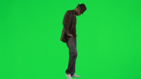 biodro : Footage of an Afro-American young man dancing with a hat and a jacket against green screen in high definition