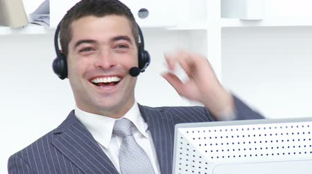 smíšené rasy osoba : Attractive businessman with a headset on working in a call center. Footage in high definition