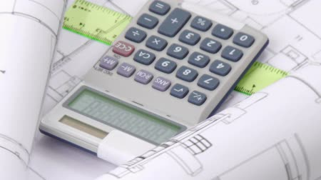 real : Close-up of a high view of plans and calculator turning in high definition