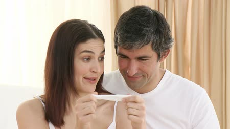 banyo : Footage in high definition of happy couple holding a pregnancy test in bedroom Stok Video