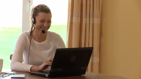 mikrofon : Cheerful woman with headset on using a laptop at home Wideo