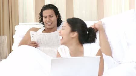 мебель : Footage in high definition of woman using a laptop and man reading a newspaper in bed