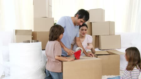 ипотека : Footage in high definition of young parents and children moving house unpacking boxes