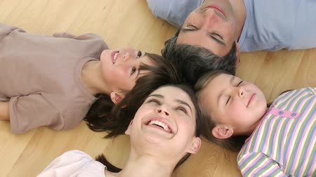 relaxační : High angle of happy family lying on floor with heads together at home. Footage in high definition Dostupné videozáznamy