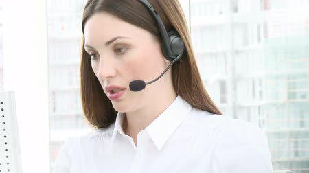 kontakt : Close-up of serious young woman working in a call center. Customer service. Footage in high definition