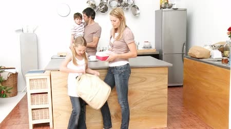 фронт : Mother giving girl the school lunch in the kitchen and father and son in the background. Footage in high definition