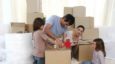 mozgás : Footage in high definition of young parents and children moving house packing boxes