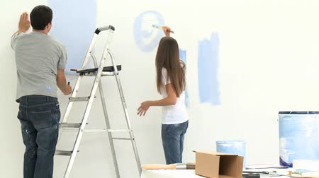 malarstwo : Young couple having fun while painting walls in a room