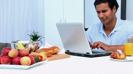 guy home : Happy man working on the laptop while having breakfast in the kitchen