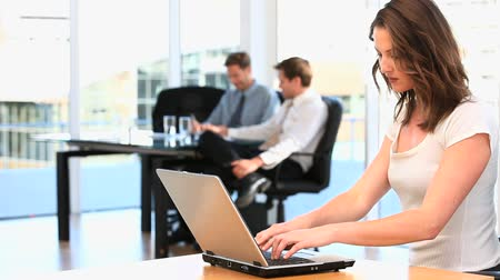 elnök : Businesswoman working on her laptop in an office with a team on the background