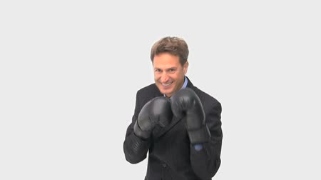 puncs : Happy businessman boxing towards the camera against a white background
