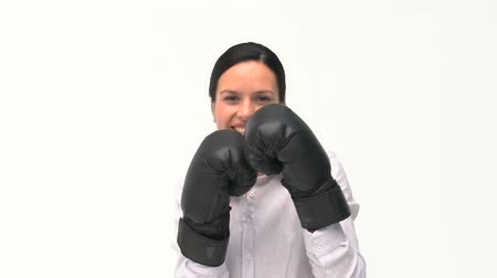glove : Smiling businesswoman boxing towards the camera against a white background Stock Footage