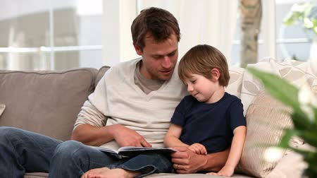 olvasás : Nice father reading a story to his young son at home Stock mozgókép