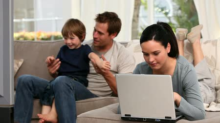televízió : Woman using laptop while her boy and husband are watching tv in the livingroom Stock mozgókép