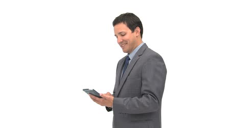 КПК : Smiling businessman using a computer tablet against a white background