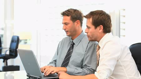 Coworkers working together on a laptop in a office Stock Footage