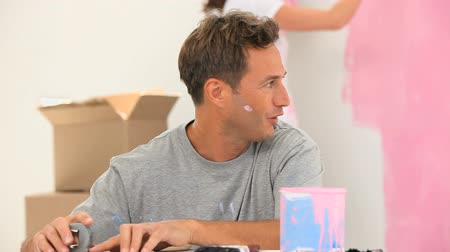 two people talking : Man talking with his wife while she is painting at home Stock Footage