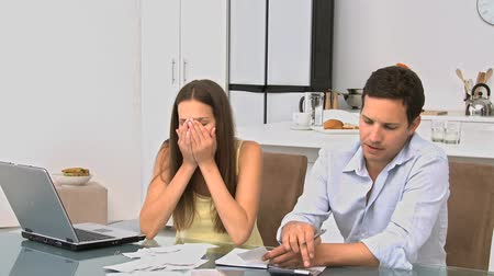 povinnost : Couple worrying about their bills while sitting at a table in the office