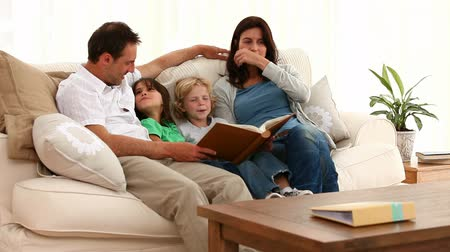 öykü : Cute family looking at an album while sitting on the sofa at home