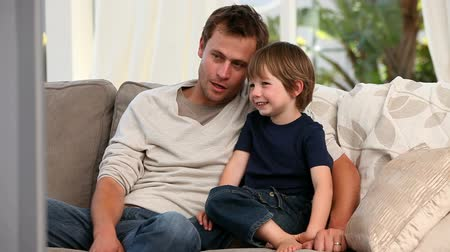 oğlum : Attentive father watching tv with his son on their sofa