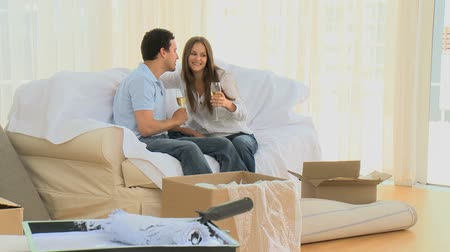 šampaňské : Young couple drinking champagne during their removal sitting on the sofa