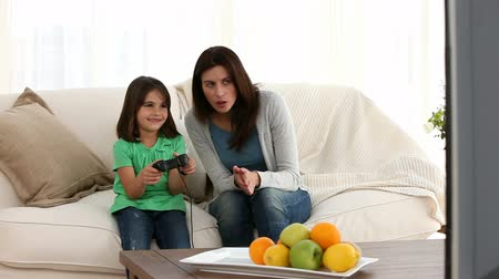 дичь : Little girl playing video games with her mother sitting on the sofa