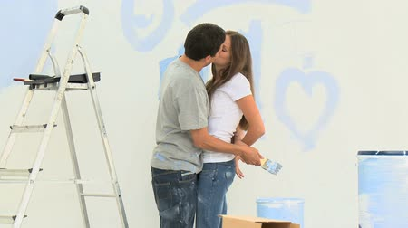 любовь : Man kissing and hugging his girlfriend during a renovation at home