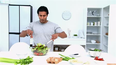 sağlıklı beslenme : Man eating while he is cooking in the kitchen
