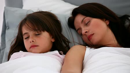 postel : Serene mother and daughter sleeping together on a bed Dostupné videozáznamy