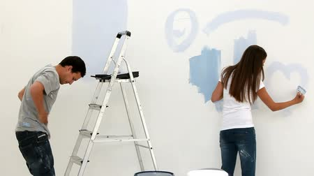 malarstwo : Woman drawing a heart on the wall while her husband painting