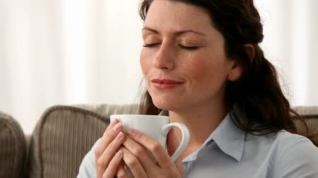 xícara de café : Woman smelling tea or coffee on the sofa