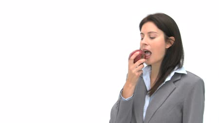 bizneswoman : Businesswoman eating an apple against a white background