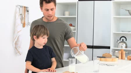 otec : A dad serving a glass of milk to his son in the kitchen