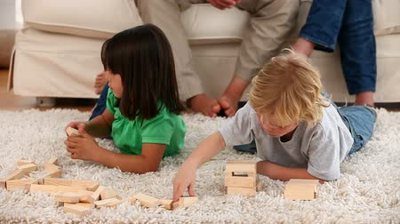 sitting room : Children playing on the floor while their parents talking each other sitting on the sofa at home Stock Footage