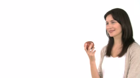 munch : Pretty woman eating an apple against a whit background Stock Footage