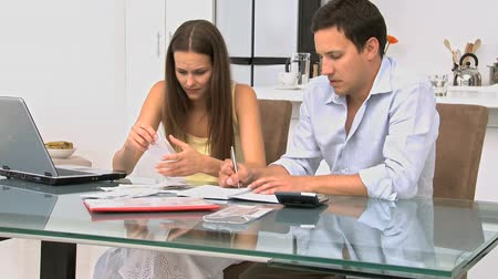 финансы : Worried couple calculating their bills while sitting at a table in the office Стоковые видеозаписи