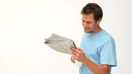 редакционный : Smiling man reading a newspaper against a white background Стоковые видеозаписи