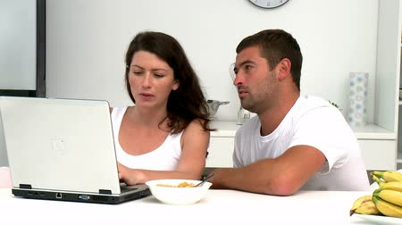 surfing the net : Concentrated couple buying on internet with a credit card sitting at a table in the kitchen