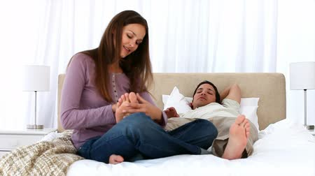 quarto doméstico : Cute woman massaging her boyfriends foot lying on the bed