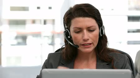 fejhallgató : Unhappy woman talking on the headphone in an office