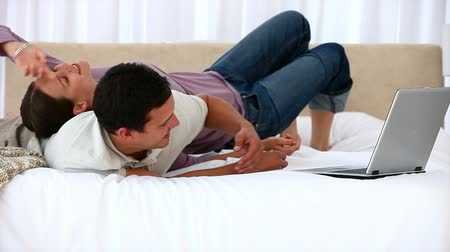 cama : Woman lying on her husband while he is working on his laptop