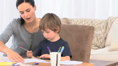 uczenie się : Adorable mother helping her son to drawing in their living room