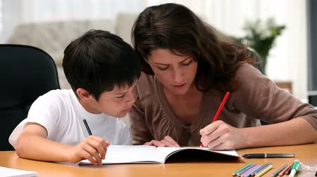 öğretim : Mom doing homework with her son in the living room
